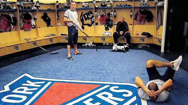 Kabina. Po tréninku je třeba důkladné protažení, jako to dělá právě Michal Rozsíval. Před Marcelem Hossou zase pózuje s hokejkou Marek Malík, věčný vtípkař.
