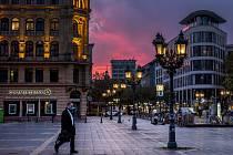 Muž s roškou se prochází kolem budovy Opery ve Frankfurtu