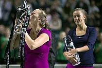Petra Kvitová líbá pohár mistryň, v pozadí ji sleduje Běloruska Azarenková.