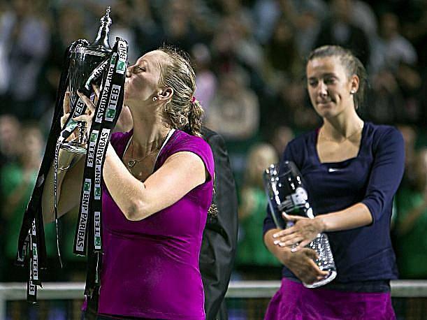 Petra Kvitová líbá pohár pro vítězku Turnaje mistryň, v pozadí ji sleduje Běloruska Azarenková.