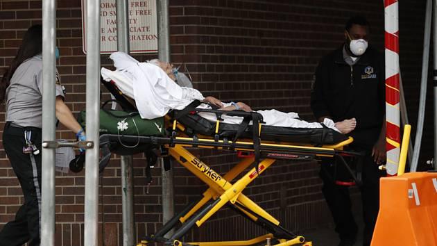 Záchranář s pacientem u nemocnice v newyorském Brooklynu 5. dubna 2020