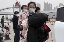 Žena v roušce držící dítě v čínském Wu-chanu (na snímku z 3. března 2020)