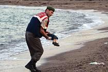 Turecký policista odnáší dítě vyplavené na pobřeží, které se utopilo během plavby imigrantů na ostrov Kos.