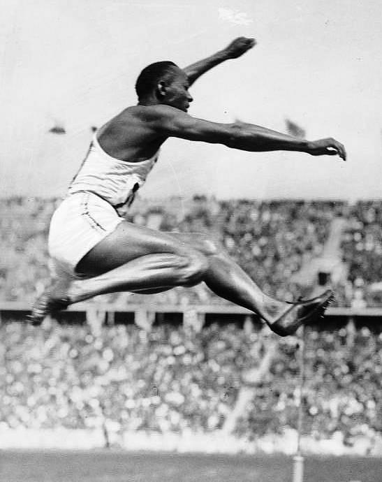 Legendární americký atlet Jesse Owens zachycen při skoku do dálky na olympiádě v Berlíně v roce 1936. Za svůj skok získal Owens jednu ze čtyř zlatých medailí, které si z Berlína odvezl.