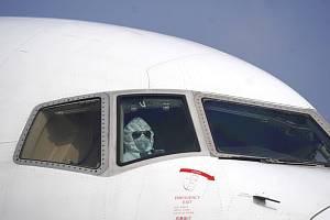 Pilot dopravního letadla v masce na mezinárodním letišti ve Wu-chanu 28. ledna 2020