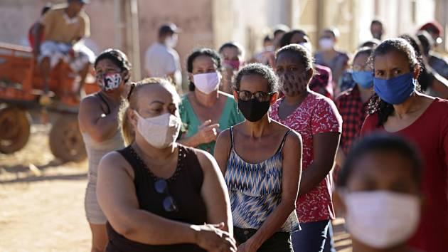 Lidé v rouškách z komunity Sol Nascente na okraji Brasílie