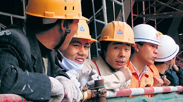 CELÁ ČÍNA STAVÍ. Olympiáda je věcí hrdosti i výdělku. Do hlavního města zamířily za prací tisíce lidí z chudého venkova.