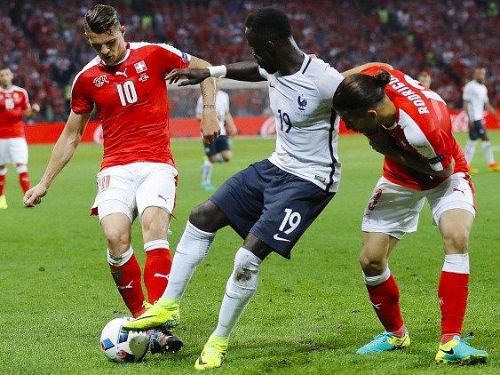 Švýcaři Xhaka a Rodriguez v souboji s Francouzem Sagnou.