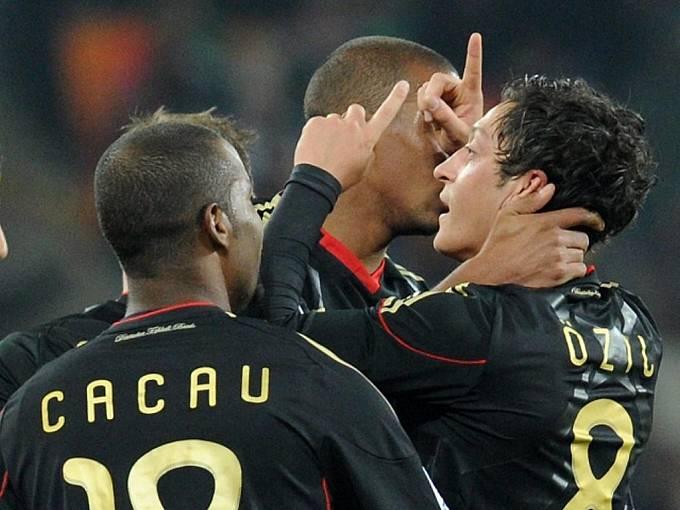 Mesut Özil (vpravo) slaví se spoluhráči Cacauem (vlevo) a Jerome Boatengem gól proti Ghaně.