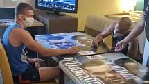 Netradiční předehra. Zápasník David Dvořák a jeho protivník Jordan Espinosa podepisují plakáty před vzájemným duelem. Věc u bojových sportů nevídaná – u jednoho stolu.
