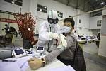 Provizorní nemocnice ve Wu-chanu - Zdravotník u pacienta provizorní nemocnice, která vznikla přebudování výstavního centra ve Wu-chanu (snímek z 18. února 2020)