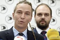 Předseda Pirátů Ivan Bartoš hovoří na tiskové konferenci poslaneckého klubu strany před jednáním Sněmovny 24. září 2019 v Praze. V pozadí vpravo je poslanec Lukáš Bartoň.
