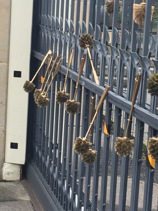 Zlaté záchodové štětky na plotě pozemku ruské ambasády.
