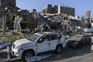 Lidé prohledávají explozí zničené budovy v libanonském Bejrútu, 5. srpna 2020