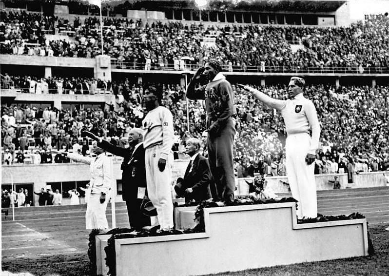 Jesse Owens na stupních vítězů po vítězství zlaté medaile ve skoku do dálky. Tím, že šlo o afroamerického sportovce, se Owens stal důvodem hněvu nacistického vůdce Adolfa Hitlera.
