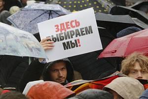 """Muž drží papír s nápisem """"Tady vybírámne my"""" na demonstraci v Moskvě"""