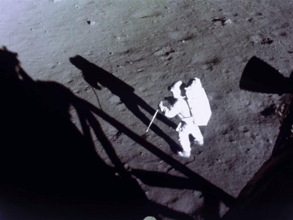 Zostřený záběr Neila Armstronga, sbírajícího vzorky měsíční horniny