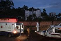 Zdravotník na lodi, která přivezla pacienta s covidem-19, sleduje jeho přesun do sanitky v brazilském přístavu Manacapuru (na snímku z 1. června 2020)