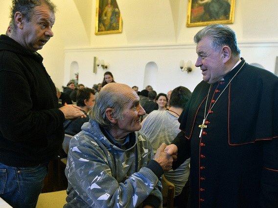 Tradiční vánoční oběd pro bezdomovce, seniory a postižené zahájil 25. prosince v arcibiskupském paláci na Pražském hradě kardinál Dominik Duka (vpravo).