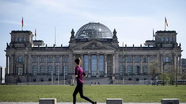 Běžkyně míjí budovu Říšského sněmu v Berlíně (na snímku z 11. dubna 2020)