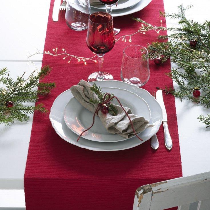Různé způsoby výzdoby svátečního stolu v typických barvách Vánoc – červené sklenice, zelené jehličí.