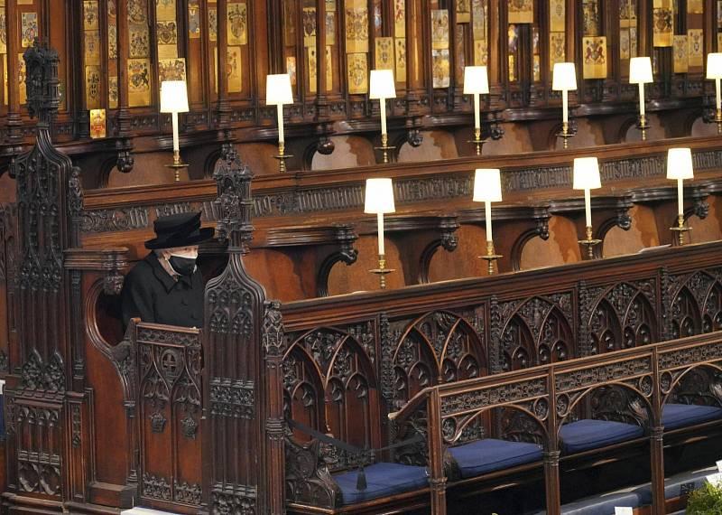 Královna Alžběta II. sedí kvůli covidovým opatřením odděleně od ostatních členů královské rodiny.