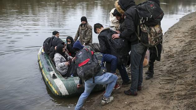 Migranti s nafukovacím člunem, na němž se přes řeku Maritsa pokouší překročit turecko-řeckou hranici na snímku z 29. února 2020