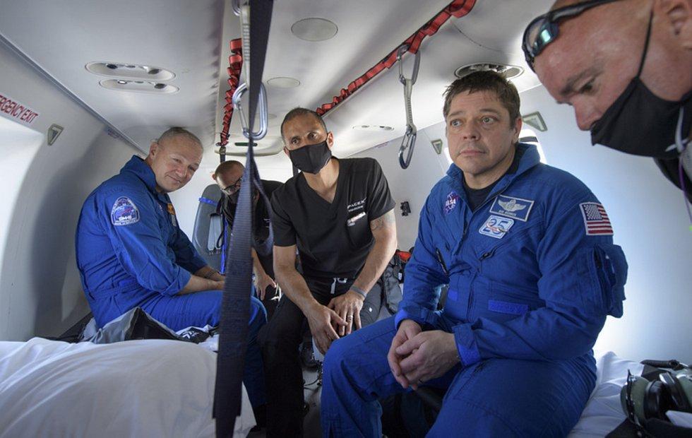 Astronauti NASA Robert Behnken (vpravo) a Douglas Hurley při cestě vrtulníkem na námořní základnu Pensacola poté, co s lodí Crew Dragon přistáli v Mexickém zálivu, 2. srpna 2020.