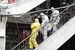 Pracovníci pohřebního ústavu odnáší z bytového domu v čínském Wu-chanu tělo člověka, který mohl zemřít na koronavirus (snímek z 1. únoru 2020).
