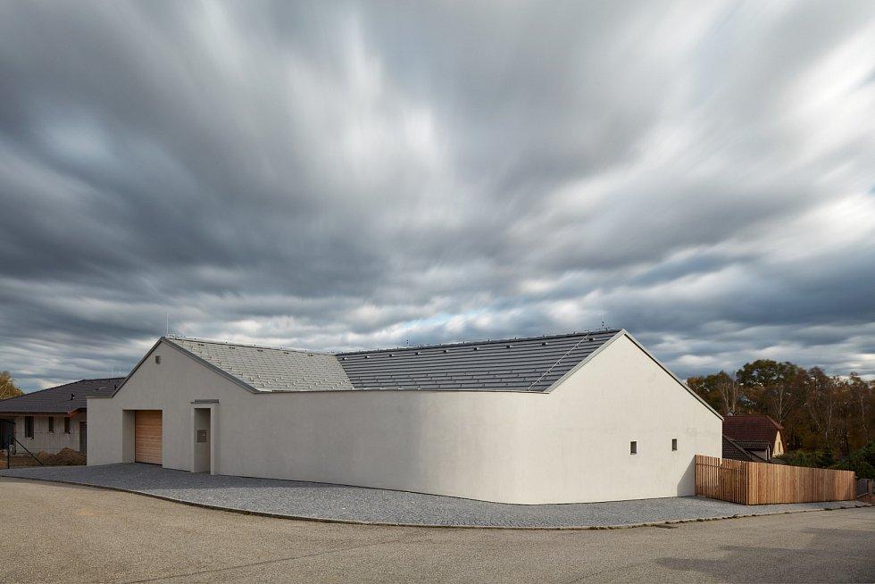 Na velkém pozemku v Litvínovicích architekti postavili minimalistický bílý objekt s netradičně zaobleným rohem místo plotu.