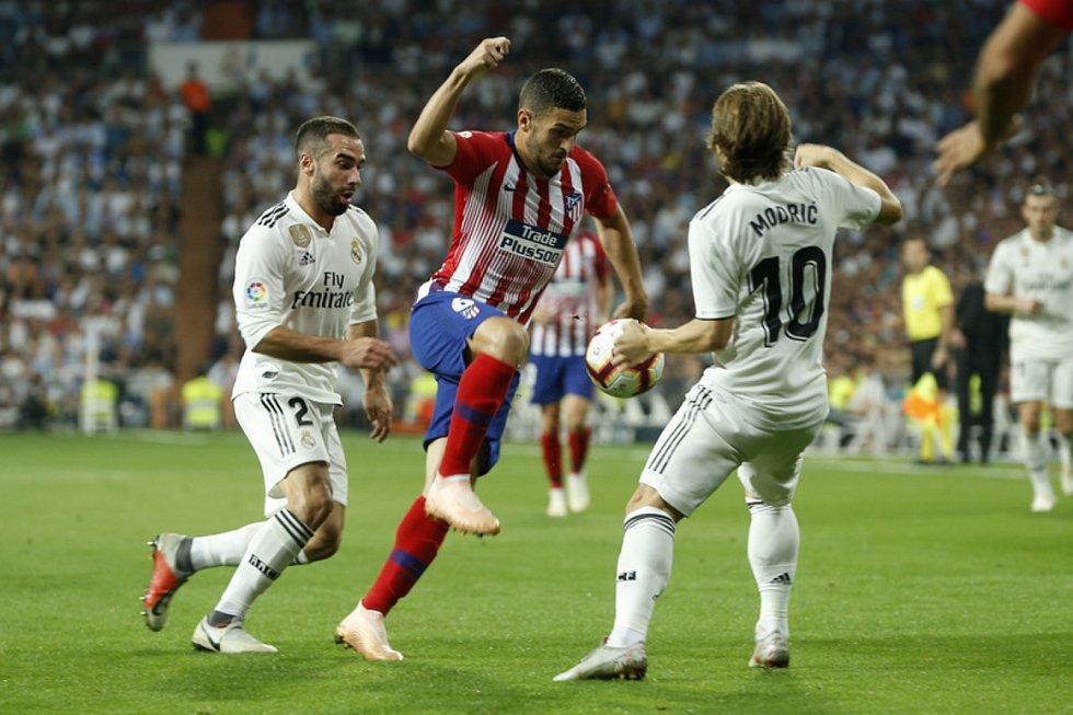 Fotbalista Atlética Madrid Koke (uprostřed) a hráči Realu Luka Modrič (vpravo) a Dani Carvajal v utkání španělské ligy.