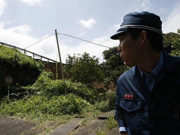 Policista hlídkuje u místa, kde se při zemětřesení sesula část trati rychlovlaku poblíž Makinohara ve středním Japonsku.