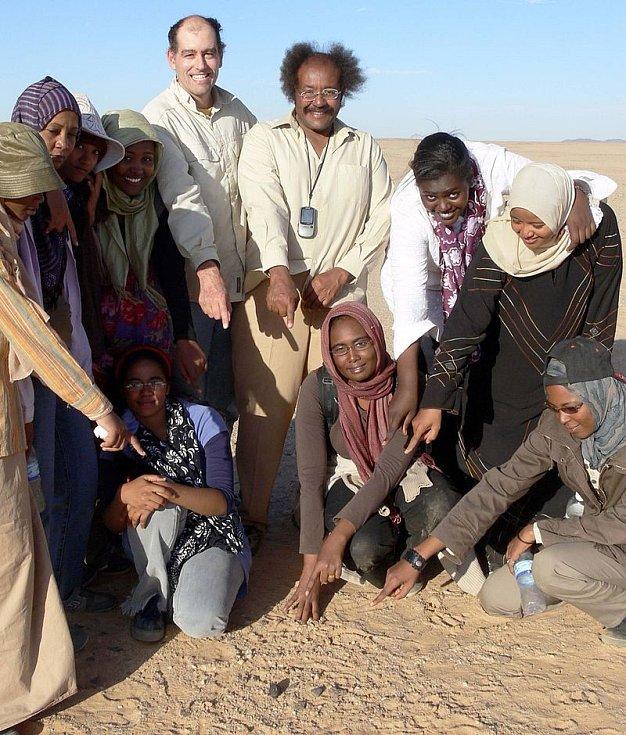 Doktor Muawia Shaddad a Peter Jenniskens z NASA ukazují spolu s několika studenty univerzity v Chartúmu na jeden z úlomků asteroidu 2008 TC3