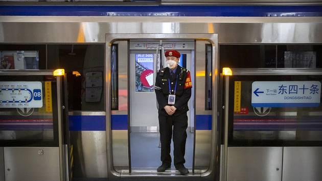 Koronavirus - člen ostrahy s rouškou na obličeji hlídkuje ve vagonu metra v Pekingu.