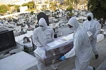 Zaměstnanci hřbitova v ochranných oblecích nesou 7. srpna 2020 rakev s ostatky ženy na hřbitově v brazilském Nova Iguacu