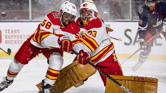 Hokejisté Calgary Flames Oliver Kylington (vlevo) a brankář David Rittich (33) v utkání s Winnipegem Jets v utkání NHL pod otevřeným nebem.