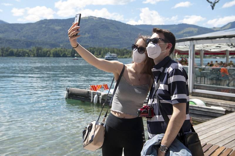 Dvojice v rouškách si pořizuje selfie u jezera v hornorakouském městečku Sankt Wolfgang