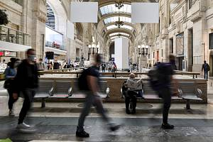 Lidé v rouškách na nádraží v Miláně