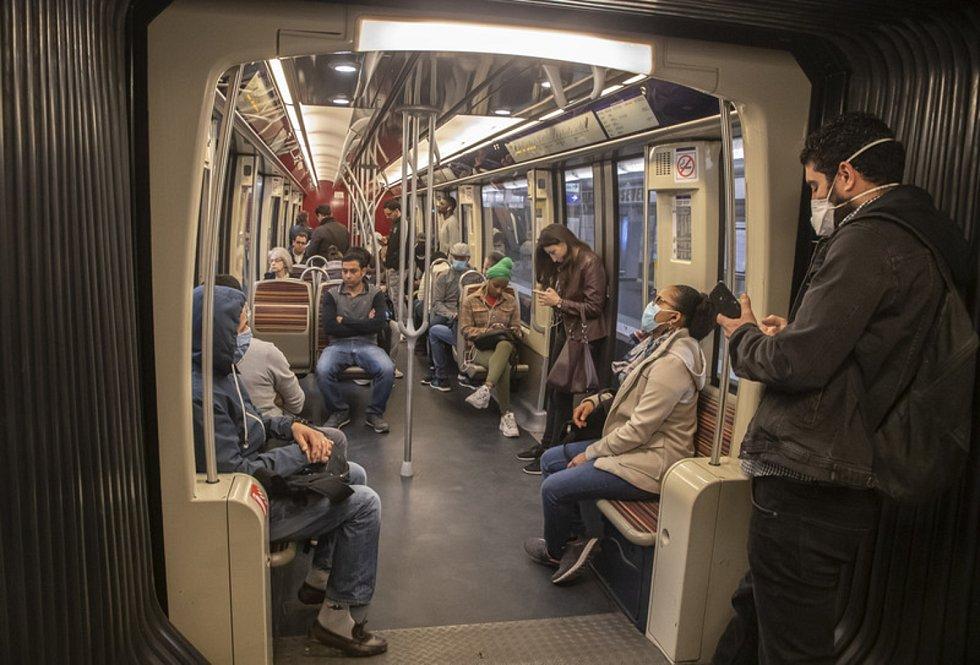 Lidé v rouškách cestují 24. dubna 2020 v pařížském metru