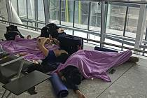 Cestující na letišti Heathrow - Cestující odpočívají na letišti Heathrow v britském Londýně