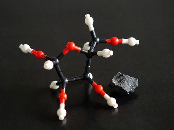 Model molekuly ribózy vedle meteoritu Murchison, sebraném v Austrálii, jenž je jednou ze dvou vesmírných hornin, kde se tento životně důležitý cukr našel