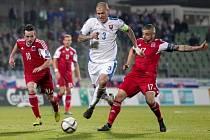 Martin Škrtel ze Slovenska (uprostřed) se snaží prosadit proti Lucembursku.