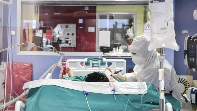 Zdravotník u pacienta na jednotce intenzivní péče v Miláně, 14. dubna 2020
