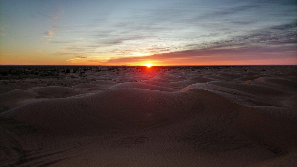 Východ slunce v poušti u kempu Zmela.