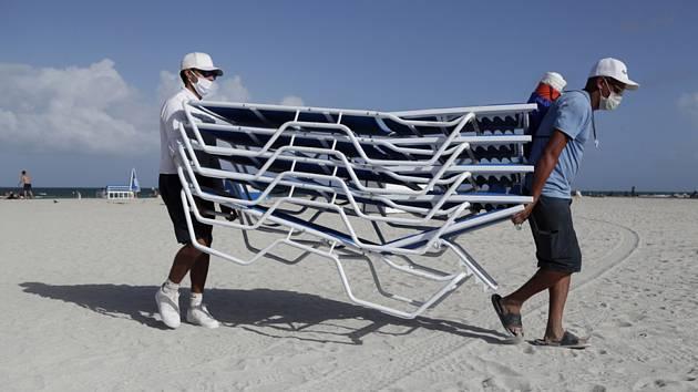 Pracovníci odklízejí lehátka z pláže v Miami Beach na Floridě před příchodem hurikánu Isaias