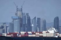 Obchodní kontejnerová loď míjí mrakodrapy v čínském městě Čching-tao. Ilustrační foto