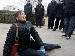 Žena pláče před budovou soudu ve městě Šitia-čuang. Ilustrační foto