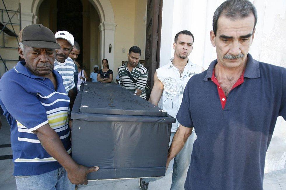 Muži nesoucí rakev z kostela během pohřbu na největším Havanském hřbitově