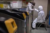 Pracovník v ochranném oděvu dává instrukce cestující v pekingském metru