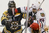 Michal Rozsíval z Chicaga (vpravo) u mantinelu odzbrojuje Toreyho Kruga z Bostonu.
